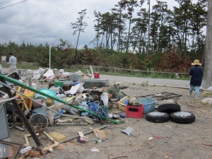 A family's entire household and family business had to be cleaned and swept out.  They weren't planning on rebuilding after the tsunami, so, everything must be sorted and memories piled up in heaps of trash to be hauled away.  Praise God, the title to his property was found amidst the rubbish and a grateful smile among the sorrow.